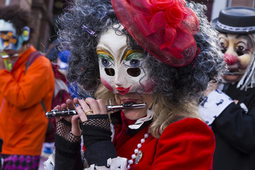 Basel carnival 2017. Spalenberg, Basel, Switzerland - March 7, 2017. Closeup of a single carnival participant in a red costume playing piccolo.