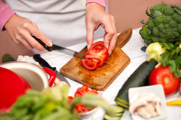 Cutting tomato on slices, preparing vegetable for salad