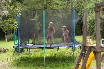 Zwei Schwestern auf dem Trampolin im Garten