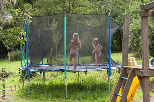zwei schwestern auf dem trampolin im garten imagens e. Black Bedroom Furniture Sets. Home Design Ideas