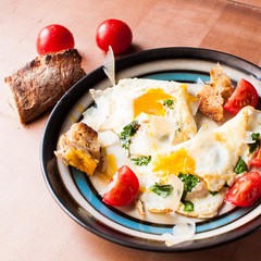 Breakfast of eggs and jamon and tomatoes.