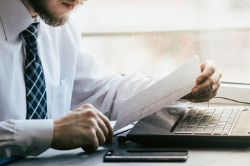 Concentrated businessman working on laptop at desk in office