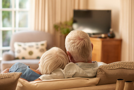 Affectionate senior couple relaxing together on their sofa at home