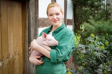 Imagepflege in der Schweinehaltung - junge Landwirtin mit Ferkel im Arm
