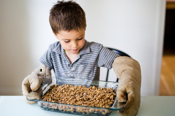 Boy wearing oven gloves, holding fruit bake