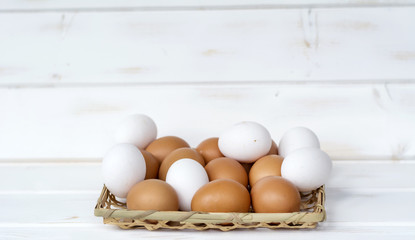 white and brown eggs in a basket on a white wooden background