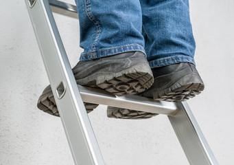 Mann steht auf Leiter