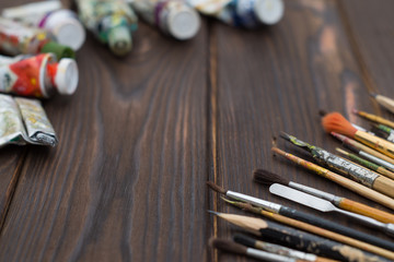 Brushes and paints are spread out on a dark wooden surface
