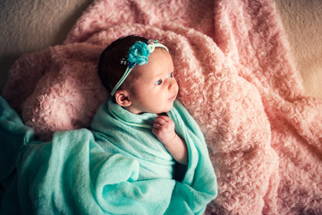 Little cute newborn baby girl in the bed