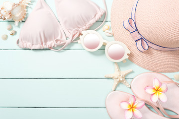 beach accessories and pink frangipani flowers on the wooden board