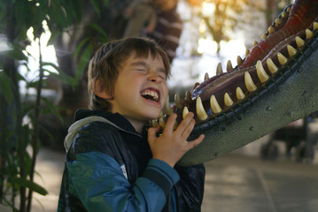 the boy stuck his head in the jaws of a dinosaur