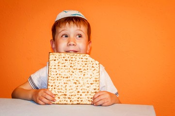 Happy little Jewish child with a kippah on his head looking forward for the Jewish holiday of Pessach. Passover illustration.