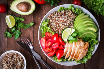 Healthy salad bowl with quinoa, tomatoes, chicken, avocado, lime and mixed greens (lettuce, parsley) on wooden background top view. Food and health. Wall mural