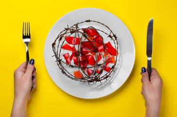 unhealthy food - barb wire and broken glass on a white plate
