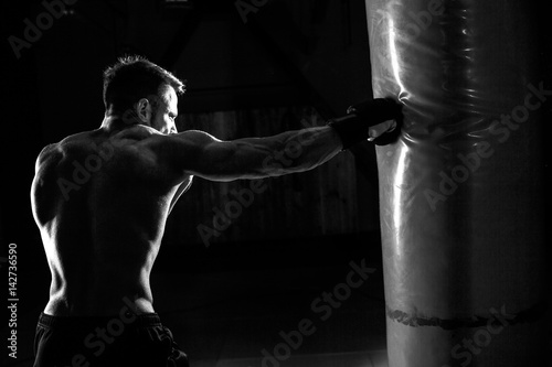 """""""Young male boxer hitting punching bag on black background ..."""