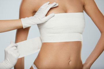 Plastic Surgery. Doctor Hands Wrapping Female Breast In Bandage
