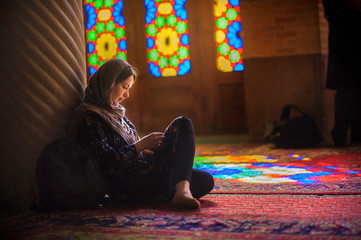 young girl in a scarf sits on a floor in the mosque, is attentive that that reads, bright multi-colored patches of light