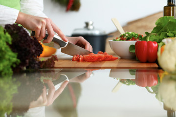 Closeup of human hands cooking vegetables salad in kitchen on the glassr table with reflection. Healthy meal and vegetarian concept