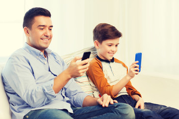 happy father and son with smartphones at home