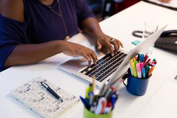 Mãos de mulher negra digitando no computador