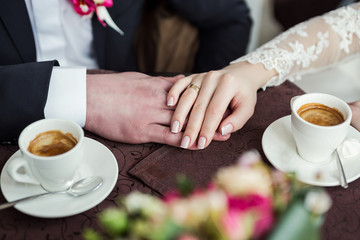 couple holding hands, loving couple drinking coffee in a coffee shop, hands close-up meeting in a cafe, a beautiful bouquet,сoffee with chocolate candies