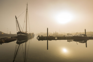 Fishing boats awaiting delayed departure in harbour due to heavy fog