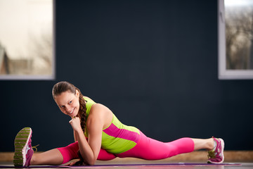 Beautiful young woman wearing colorful sportswear doing yoga or pilates exercise, Splits, Full length