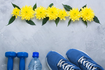 Summer flatlay composition with sport equipment and flowers.