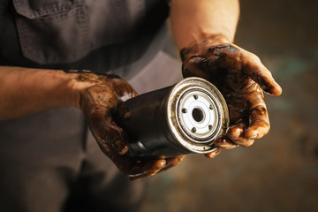 Auto mechanic with dirty hands and oil filter. Service maintenance.