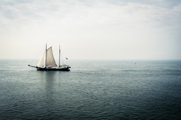 Sailboat on sea against cloudy sky