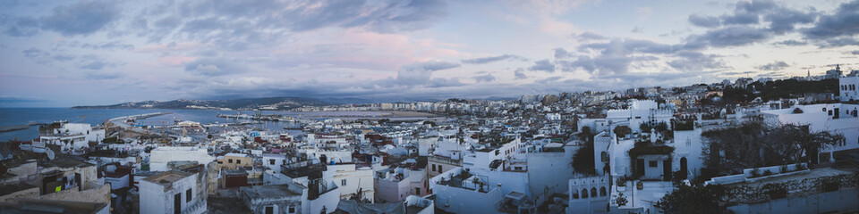 Panoramic view of cityscape against cloudy sky during sunset