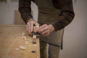 Midsection of carpenter shaving wood in workshop