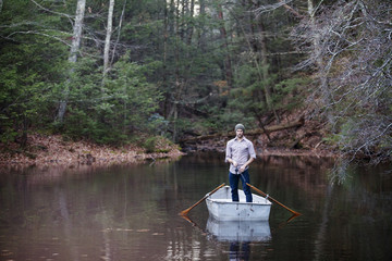 Man fishing while standing in boat on lake at forest