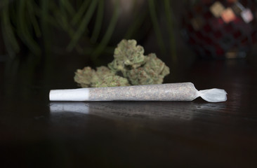closeup of rolled marijuana weed joint on wooden background