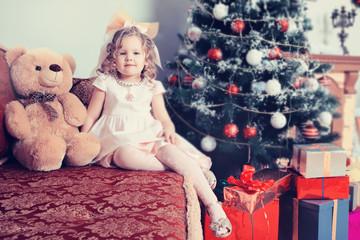 Girl sitting near Christmas tree on sofa with Teddy bear.