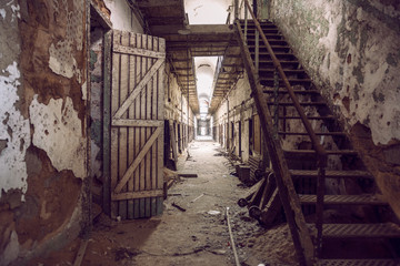 Abandoned prison cell walkway with old rusty stairs, doors and peeling walls. Philadelphia Eastern State Penitentiary.