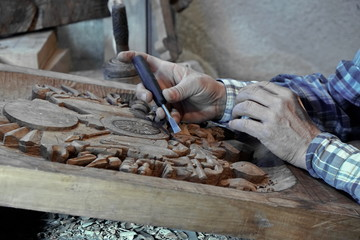Wood carving. Carver with chisel