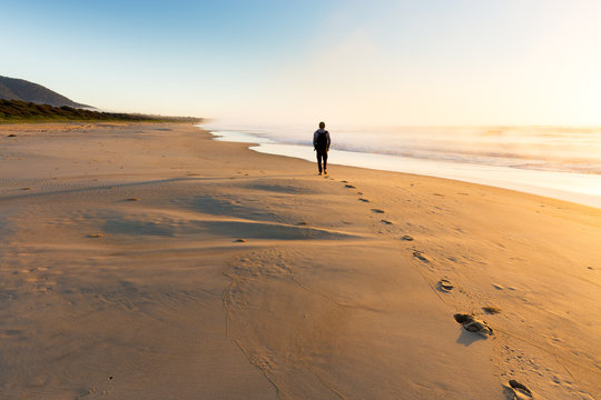 A person walking on a beautiful beach leaves a trail of footprints as the sunrise illuminates mist rising from the sea in golden light.