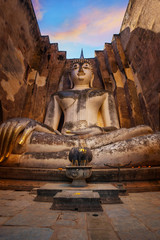 Seated Buddha image at  Wat Si Chum temple in Sukhothai Historical Park, a UNESCO world heritage site in Thailand