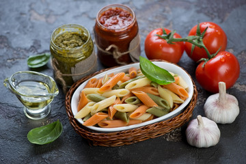 Three-colored penne pasta with different pesto sauces and cooking ingredients, closeup
