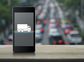 Truck flat icon on modern smart phone screen on wooden table over blur of rush hour with cars and road, Business transportation service concept