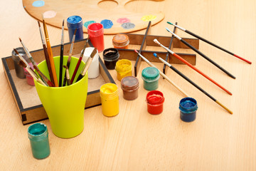 Drawing set Palette with laying on paints and cup with paintbrushes