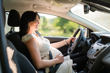 Pregnant woman driving her car, wearing seat belt.