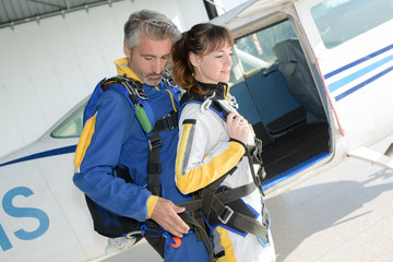 Man and woman preparing for tandem parachute jump