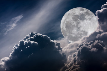 Nighttime sky with clouds and bright full moon with shiny.  Vintage tone effect.