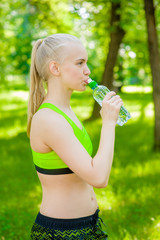 Sporty woman drinking water outdoor