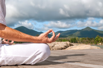 Close up of man's hands meditating outdoors in beautiful mountains landscape