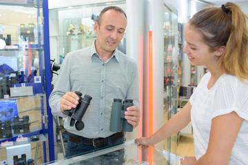 Man in shop holding two pairs of binoculars