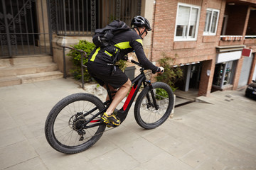 Side shot of male cyclist wearing cycling clothing and protective gear speeding on streets riding his pedal-assist electric bike, about to jump down concrete stairs. Exteme sports and adrenaline