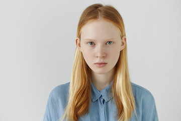 Youth and beauty concept. Portrait of beautiful Caucasian teenage girl wearing her long blonde hair back looking at camera with serious facial expression. Cute young woman with freckles posing indoors